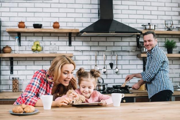 Mãe, ensinando, dela, filha, usar, tablete digital, enquanto, pai, preparando alimento, em, cozinha