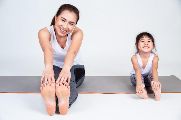 Mãe ensinando filha a alongar os músculos da perna.