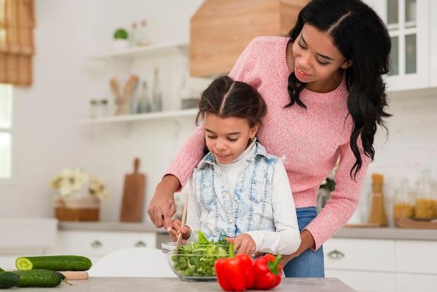 Mãe ensinando filha a cozinhar