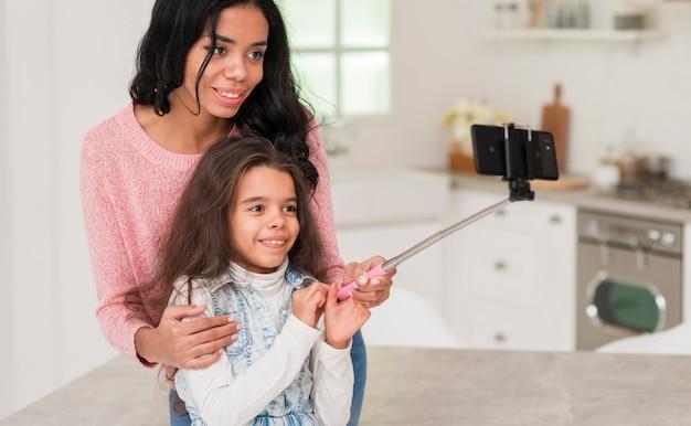 Mãe ensinando filha a tirar selfie
