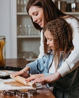 Mãe ensinando filha a usar o rolo de massa