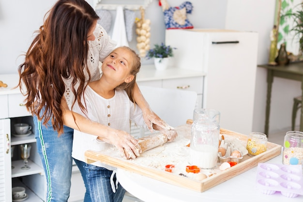 Mãe ensinando filha a usar rolo de cozinha