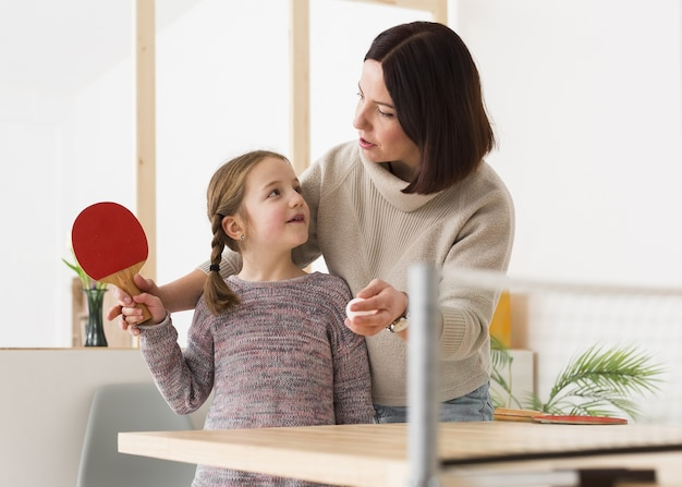 Mãe ensinando filha pingue-pongue
