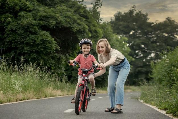 Mãe ensinando filho a andar de bicicleta feliz menino bonito com capacete aprende a andar de bicicleta