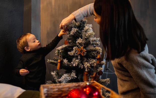 Mãe ensinando filho a decorar árvore de natal