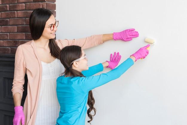 Mãe ensinando menina a pintar parede