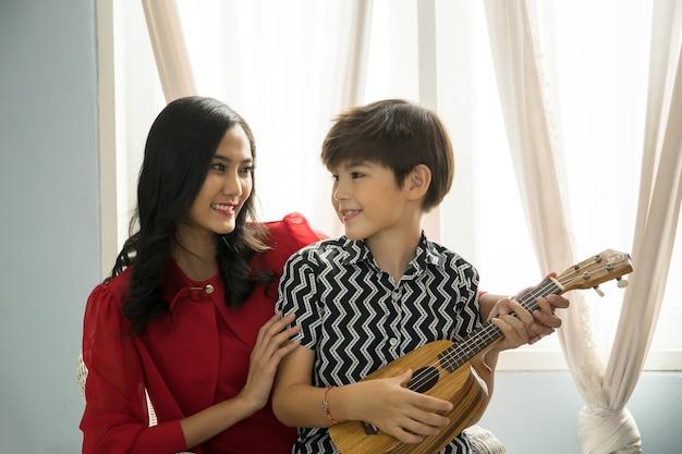 Mãe ensinando o filho a tocar violão na sala de estar.