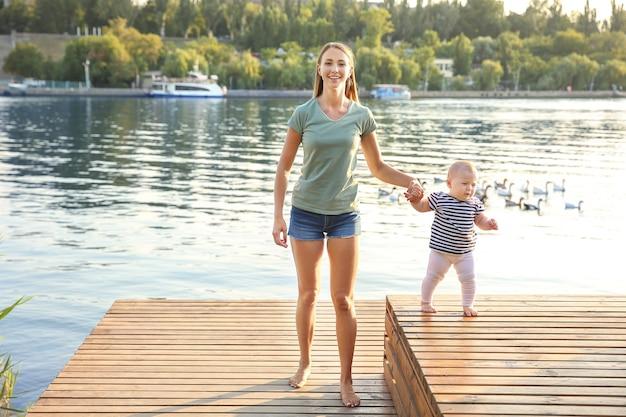 Mãe ensinando seu bebê a andar perto do rio