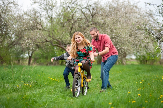Mãe ensinando seu filho a andar de bicicleta pelo seu exemplo