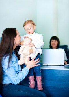 Mãe entretendo a filha no consultório médico