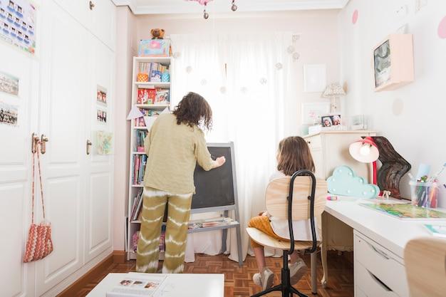 Mãe escrevendo na lousa para filha