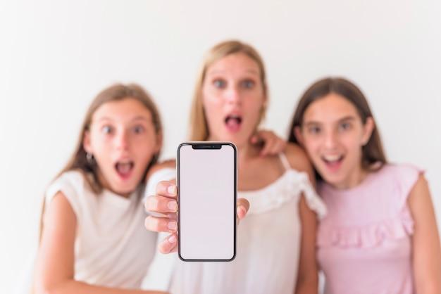 Mãe espantada e filhas segurando smartphone com tela em branco