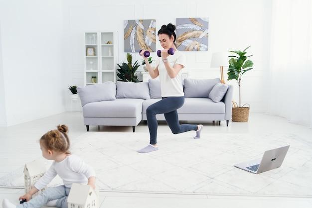 Mãe esportiva fazendo exercícios com halteres e sua linda filha macia brincando com brinquedos em primeiro plano.