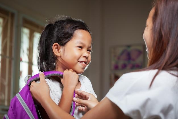 Mãe está ajudando sua filha a se preparar para a escola