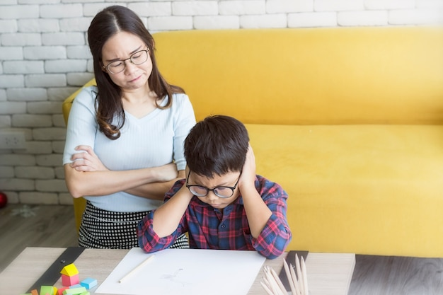 Mãe está com raiva de seu filho fazendo lição de casa