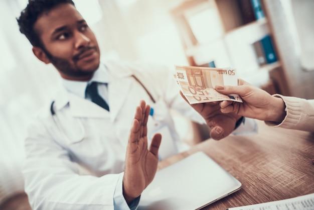 Mãe está dando dinheiro para o médico. doutor está se recusando.