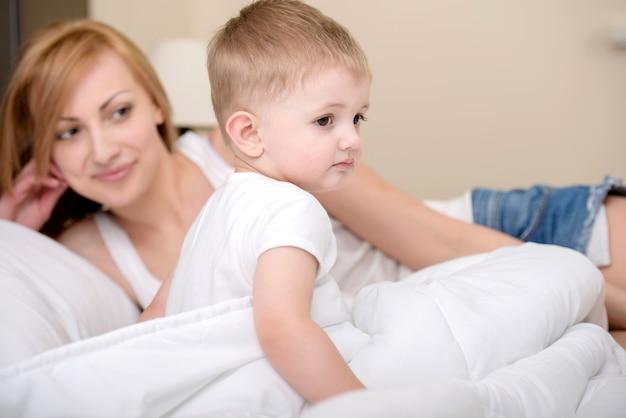 Mãe está deitado perto do filho pequeno e sorrir.