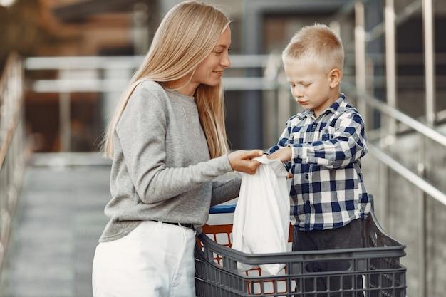 Mãe está dirigindo um carrinho. família em um estacionamento perto de um supermercado.
