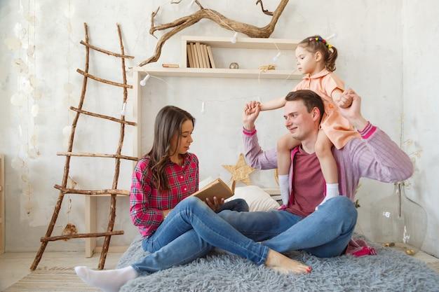 Mãe está lendo um livro e sorrindo enquanto passa algum tempo juntos em casa