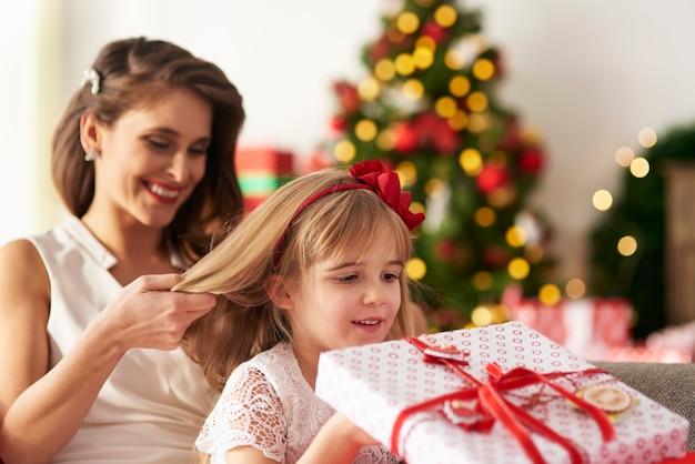 Mãe está penteando o cabelo das meninas