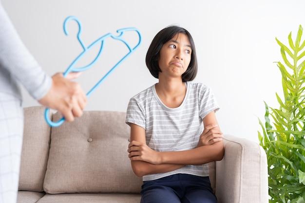Mãe está punindo a filha batendo em um cabide enquanto está sentada no sofá por causa de mau comportamento