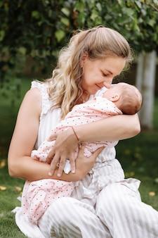Mãe está segurando e abraçando a filha dela ao ar livre num dia de verão