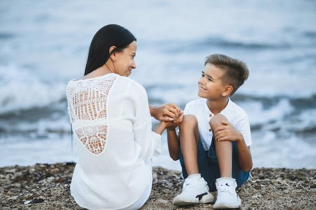 Mãe está sentada com o filho na praia rochosa, perto do mar tempestuoso, vestida com roupas brancas casuais