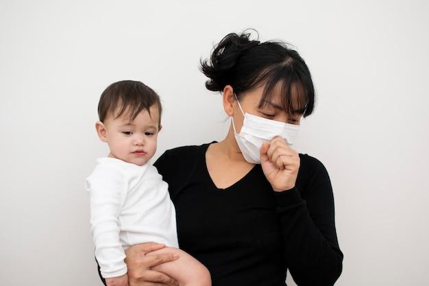 Mãe está tossindo na máscara enquanto carregava seu filho
