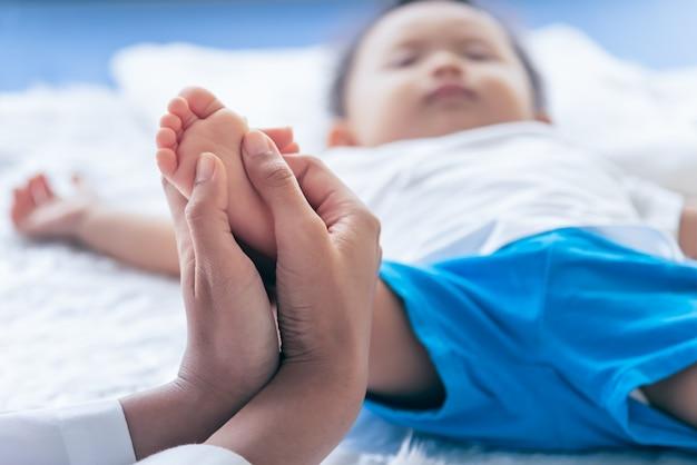 Mãe está usando as mãos para massagear os pés da criança, a fim de estimular o desenvolvimento do cérebro