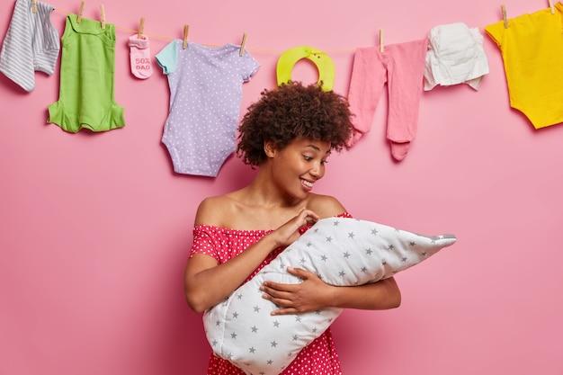 Mãe étnica feliz e carinhosa admira que sua querida filha pequena tem uma expressão alegre, gosta de brincar e cuidar do recém-nascido estando ocupada o tempo todo