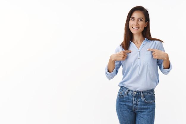 Mãe européia confiante alegre apontando a si mesma, indicar corpo, gabar-se de suas realizações, sorrir, voluntária, ajudar a administrar negócios, sorrir encantada, ficar em pé, parede branca autoconfiante