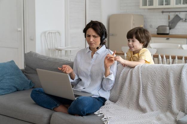 Mãe exausta, sentada no sofá em casa, trabalhando no laptop, criança distraída e pedindo atenção
