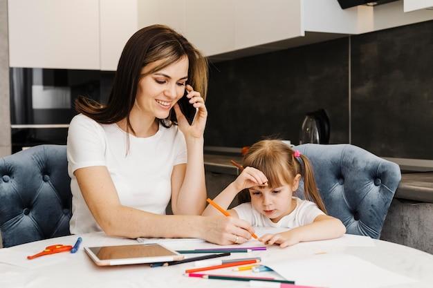 Mãe falando ao telefone e ajudando a filha