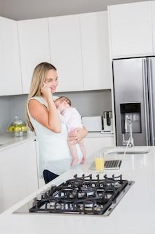 Mãe falando no celular enquanto carregava seu bebê na cozinha