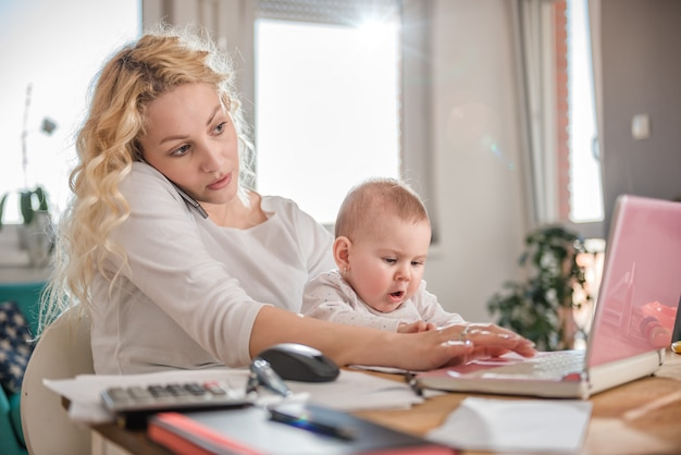 Mãe falando no telefone inteligente em casa, escritório