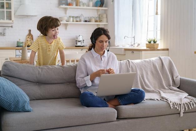 Mãe falando no trabalho remoto de videochamada no laptop de casa com a criança. crianças fazem barulho mostram língua
