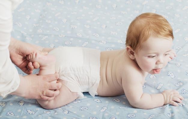 Mãe faz massagem para criança pequena