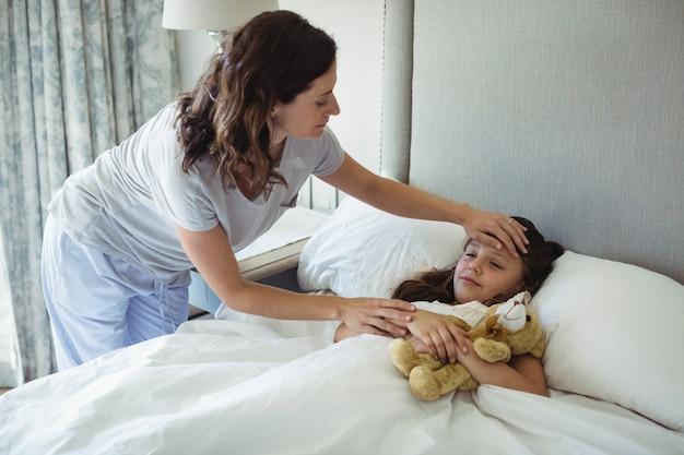 Mãe fazendo a filha dormir no quarto