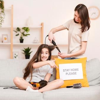 Mãe fazendo cabelo de menina em casa