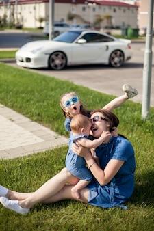 Mãe fazendo cócegas na filha, sentada em um jardim