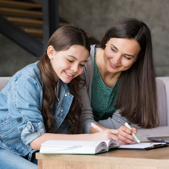 Mãe fazendo lição de casa com a filha
