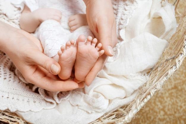 Mãe fazendo massagem nos pés para seu bebê recém-nascido
