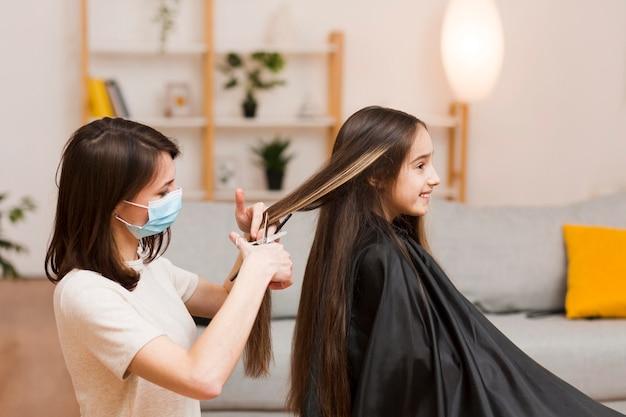 Mãe fazendo o corte de cabelo da menina