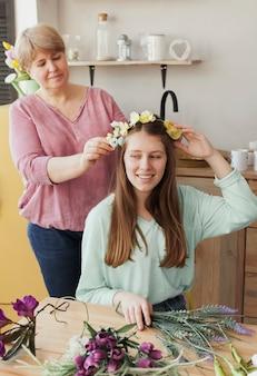Mãe fazendo uma grinalda floral para filha