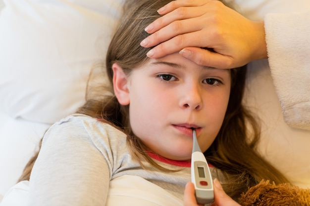 Mãe febre verificação de sua filha no quarto