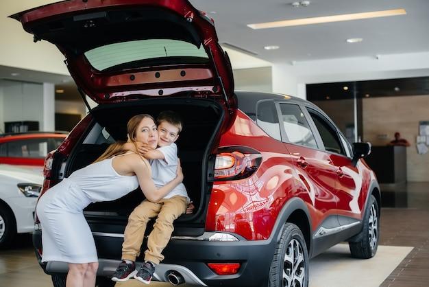 Mãe feliz abraça o filho depois de comprar um carro novo em uma concessionária