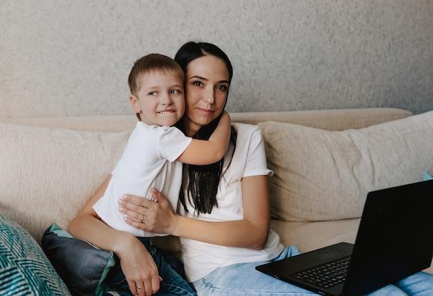 Mãe feliz abraça seu filho enquanto está sentado no sofá em frente ao laptop