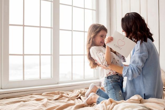 Mãe feliz, abraçando a filha com cartão