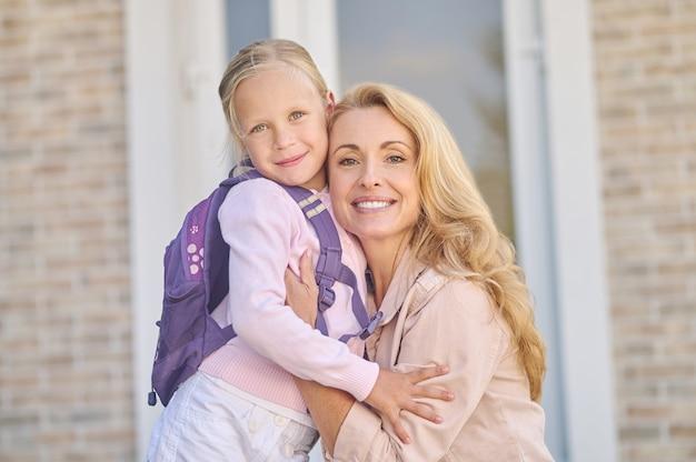 Mãe feliz abraçando a filha perto de casa