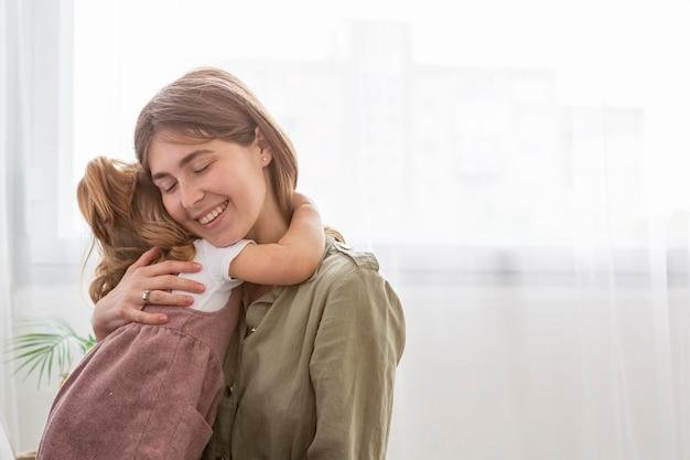 Mãe feliz, abraçando a filha